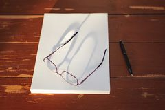 A stack of blank sheets of paper, a pen and glasses on a Red wooden table stock image