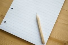 A stack of blank striped paper from a school notebook with a simple black small pencil for writing, space for text. Selective focus, a stack of blank striped stock image