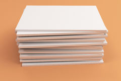 Stack of blank white closed brochure mock-up on orange background. Magazine cover template. 3D rendering illustration Royalty Free Stock Photos