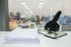 Stack of blank white paper with big office punch Stock Photos