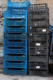 A stack of blue and black empty plastic boxes for storing and transporting vegetables and fruits. A pile of empty black and blue plastic boxes used to store and royalty free stock photos