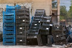 A stack of blue and black empty plastic boxes for storing and transporting vegetables and fruits. A pile of empty black and blue plastic boxes used to store and royalty free stock photography