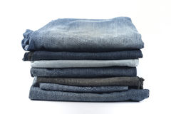 Stack of Blue and Black Jeans on White Background. Stock Photography