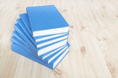 Stack of blue books. On wooden floor Stock Image