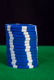 Stack of blue chips on a green playing table Royalty Free Stock Image