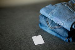 Pile of various shades of blue jeans with price lable. Stylish trandy denim clothes background. Stack of blue demin in retail store for sale stock images