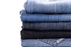 Stack of blue jeans. Closeup on white background stock image