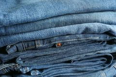 Stack of blue jeans as background stock images