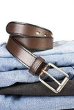 Stack of blue jeans with brown belts Stock Image