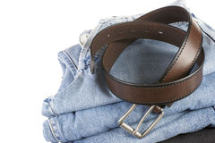 Stack of blue jeans with brown belts Royalty Free Stock Photo