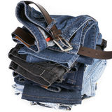 Stack of blue jeans with brown belts. Various shades of blue jeans with brown belts on a white background royalty free stock photos