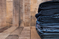 Stack of blue jeans on old wood background Stock Images