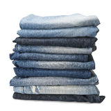 Stack of blue jeans over a white background. Stack of old and worn blue jeans over a white background royalty free stock photography