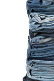 Stack of blue jeans over a white background Royalty Free Stock Photography