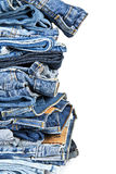 Stack of blue jeans over a white background. Stack of old and worn blue jeans over a white background stock photography
