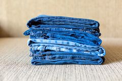 Stack of blue jeans.Shades of denim fabric. Several folded denim clothes are on the sofa. Shades of blue denim fabric stock photo