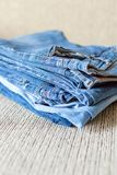 Stack of blue jeans.Shades of denim fabric. Several folded denim clothes are on the sofa. Shades of blue denim fabric royalty free stock photography