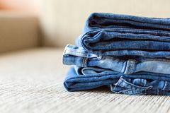 Stack of blue jeans.Shades of denim fabric. Several folded denim clothes are on the sofa. Shades of blue denim fabric royalty free stock image