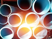 Stack of blue pvc pipes with sunbeam stock photography