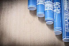Stack of blue rolled construction drawings on wooden board horiz Stock Photos