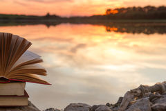 Stack of book and Open hardback book on blurred nature landscape backdrop against sunset sky with back light. Copy space, back to. School. Education background royalty free stock photo
