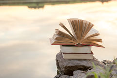 Stack of book and Open hardback book on blurred nature landscape backdrop against sunset sky with back light. Copy space, back to. School. Education background Royalty Free Stock Image