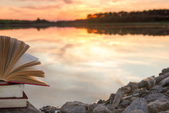 Stack of book and Open hardback book on blurred nature landscape backdrop against sunset sky with back light. Copy space, back to Royalty Free Stock Image