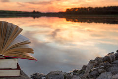 Stack of book and Open hardback book on blurred nature landscape backdrop against sunset sky with back light. Copy space, back to Royalty Free Stock Images