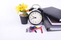 Stack of book with ticking vintage clock, artificial flower plant and colorful crayon on white table. Stock Photo