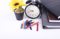 Stack of book with ticking vintage clock and colorful crayon on white table Stock Photos