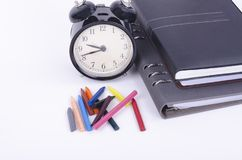 Stack of book with ticking vintage clock and colorful crayon on white table. Stock Photo
