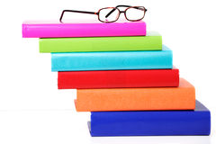 Stack of books. Staggered stack of colorful hardback books with horn rim reading glasses Stock Photo