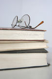 Stack of books. Eye wear atop a stack of books Royalty Free Stock Images
