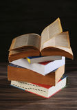 Stack of books. Open book on black background, studio shot Royalty Free Stock Photography