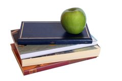 Stack of books. With a green apple on top in white background stock photo