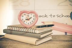 Stack of books and an alarm clock on wood Royalty Free Stock Photo