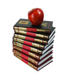 A stack of books and apple. Shiny red apple lying on a pile of books Royalty Free Stock Photography