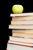 Stack of books and apple On a black background Royalty Free Stock Photography
