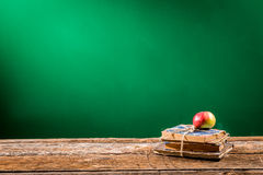 Stack of books and an apple in a classroom Royalty Free Stock Images
