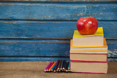 Stack of books, apple and color pencils Royalty Free Stock Images