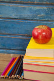 Stack of books, apple and color pencils Stock Images