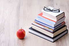 Stack of books with apple and glasses Royalty Free Stock Image