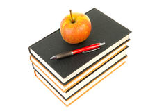 Stack of books with apple and pen Royalty Free Stock Image
