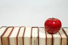 Stack of books and apple on the table. Copy space for text. Selective focus. Knowledge concept Royalty Free Stock Images