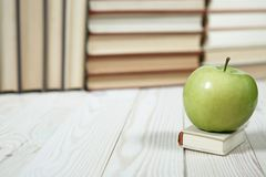 Stack of books and apple on the table. Copy space for text. Selective focus. Knowledge concept Stock Images
