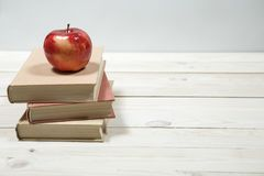Stack of books and apple on the table. Copy space for text. Selective focus. Knowledge concept Royalty Free Stock Image