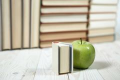 Stack of books and apple on the table. Copy space for text. Selective focus. Knowledge concept Stock Image