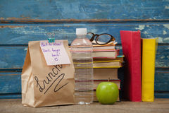 Stack of books, apple, water bottle, spectacles and lunch bag Stock Photography