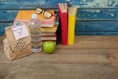 Stack of books, apple, water bottle, spectacles and lunch bag Royalty Free Stock Image