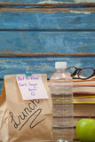 Stack of books, apple, water bottle, spectacles and lunch bag Royalty Free Stock Images